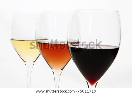 Three elegant crystal wine glasses with red, rose and white wine isolated on white background.