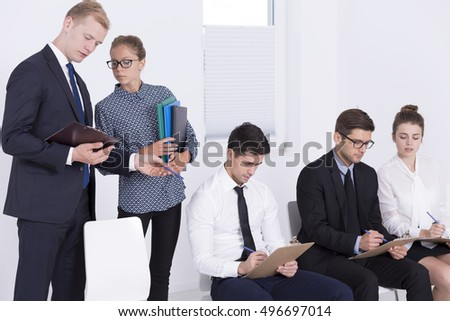 Three elegant people writing employment test, two managers standing over them and discussing
