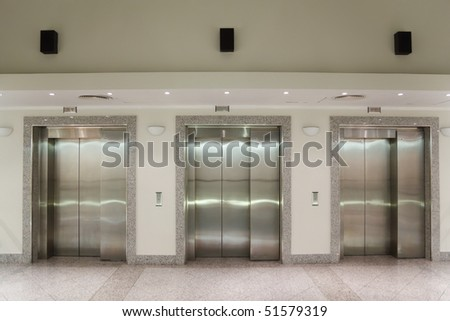 Three elevator doors in corridor of office building stock photo