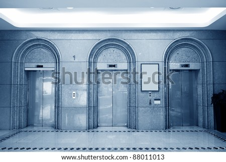 Three elevator doors in corridor of office building