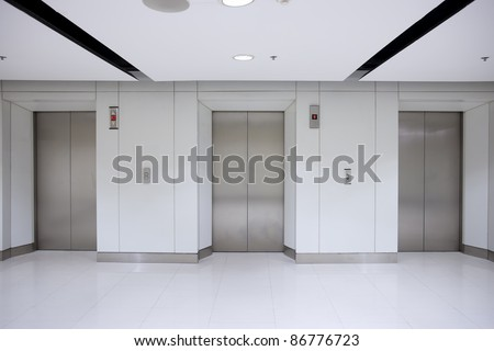 Three elevator doors in office building