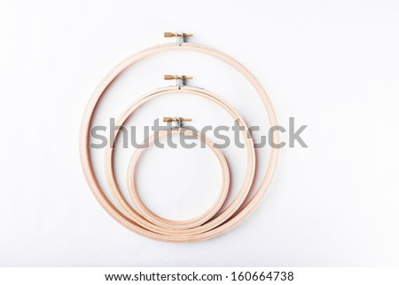Three embroidery hoops for needlework and sewing arts and creative crafts arranged on white background - stock photo