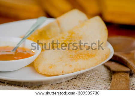 Three empanadas nicely arranged on white platter next to small salsa bowl and rustic background . - stock photo