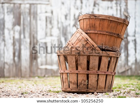 Three empty apple orchard baskets stacked in front of the barn - stock photo
