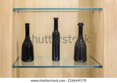Three Empty black bottles on a glass shelves in a wooden cabinet  - stock photo