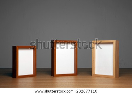 three empty(blank) wood photo frames(teak, cherry, oak) on the wood table(desk) at the studio. - stock photo