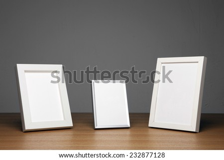 three empty(blank) wood photo frames(white) on the wood table(desk) at the studio. - stock photo