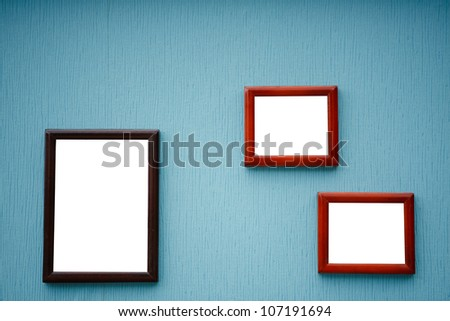 Three empty frame of picture on the blue wall - stock photo