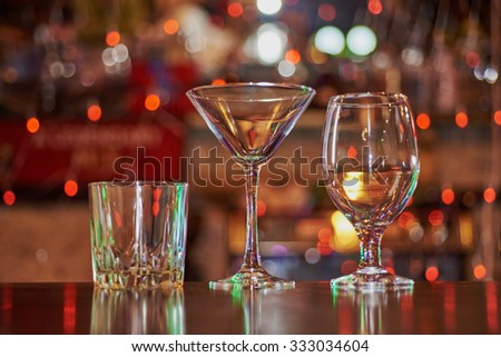 three empty glasses (martini, cocktail, whiskey) on the wooden bar on the background bokeh round red lights garland - stock photo