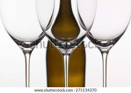 Three empty glasses of wine and brown bottle on the white background - stock photo