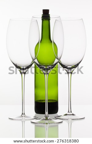 Three empty glasses of wine and green bottle on the white background - stock photo