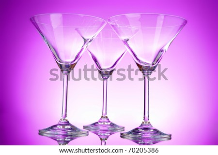 Three empty martini glasses on purple background