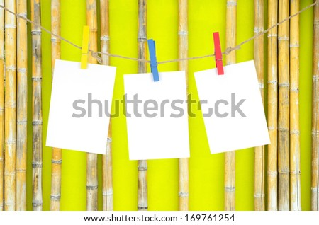 Three empty white photo frames hanging with clothespins on bamboo wall background - stock photo