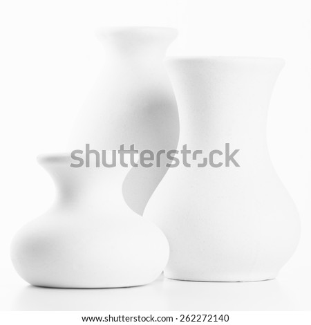 Three empty white unglazed ceramic vases on white background. Black and white image, high key. Shallow DOF, focus on middle vase. - stock photo