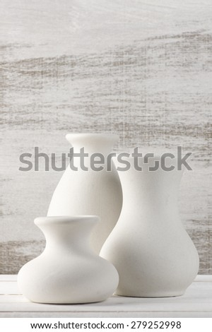Three empty white unglazed ceramic vases on white wooden table against rustic wooden wall. Shallow DOF, focus on middle vase. - stock photo