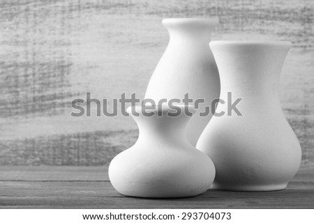 Three empty white unglazed ceramic vases on wooden table against rustic wooden wall. Black and white image. Shallow DOF, focus on front small vase.