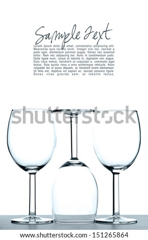 Three empty wine glasses backlit against white background with copy space - abstract. - stock photo