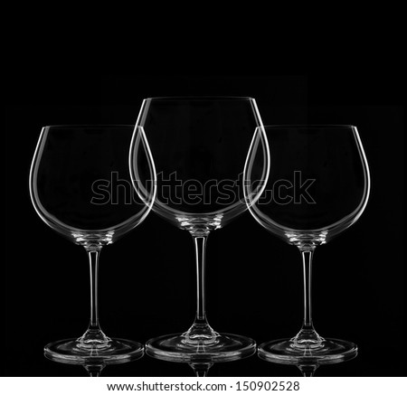 Three Empty Wine Glasses on Black Background - stock photo