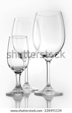 Three empty wine glasses overlapped isolated white. - stock photo