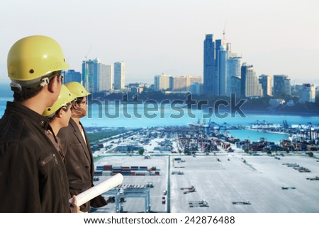 three engineer team standing in front of cranes at the container port terminal with big city background - stock photo