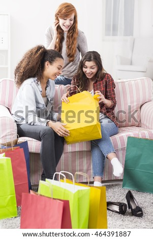 Three enthusiastic teenagers opening colourful shopping bags and laughing