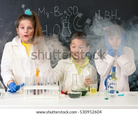 three excited funny children after chemical experiment in lab
