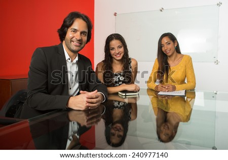 Three executives working at a business meeting, looking at came