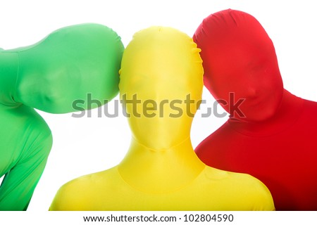 Three faceless people wearing bright, colorful body suits.  Red, green and yellow. - stock photo
