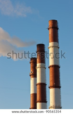 Three factory pipes with a smoke against the sky