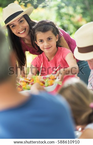 Three family having lunch in the garden in summer. A little girl serving a dish with melon and tomatoes. Mom helps her