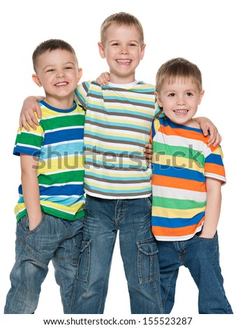 Three fashion cute boys are standing together on the white background