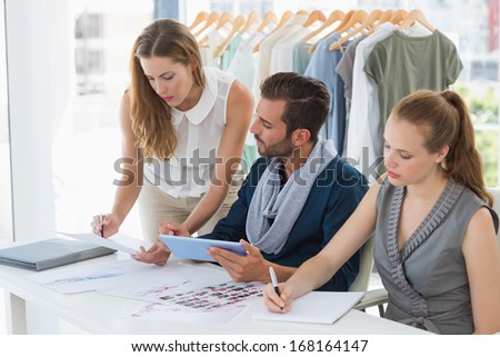 Three fashion designers discussing designs in a studio