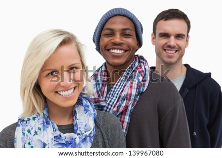 Three fashionable friends looking at camera and smiling on white background - stock photo