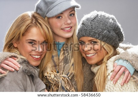 Three Fashionable Teenage Girls Wearing Cap And Knitwear In Studio - stock photo