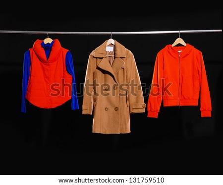 Three female dress, coat isolated on hanging-black background - stock photo