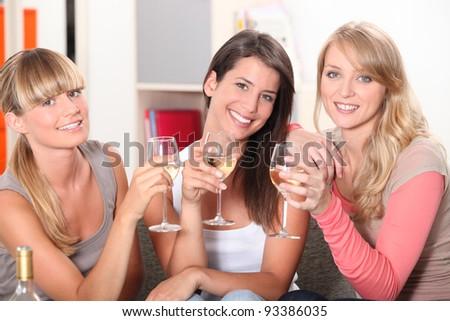 Three female friends drinking wine on sofa - stock photo