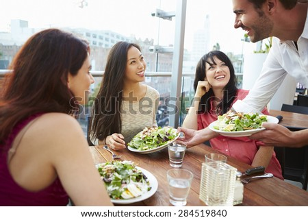 Three Female Friends Enjoying Lunch At Rooftop Restaurant - stock photo