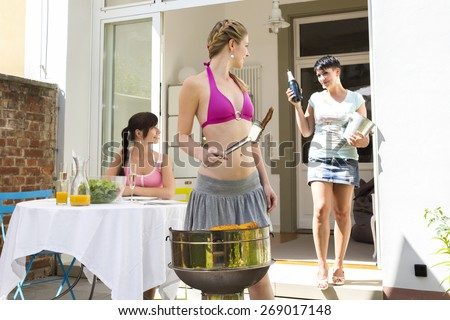 Three female friends having barbecue on terrace