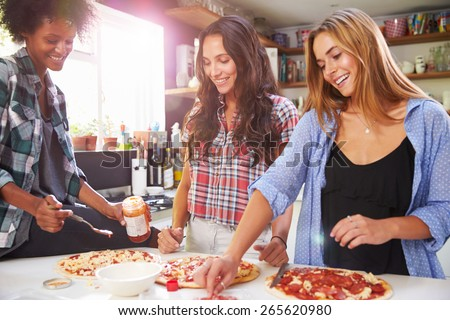 Three Female Friends Making Pizza In Kitchen Together - stock photo