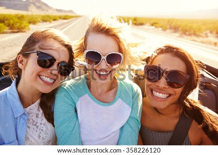 Three Female Friends On Road Trip In Back Of Convertible Car - stock photo