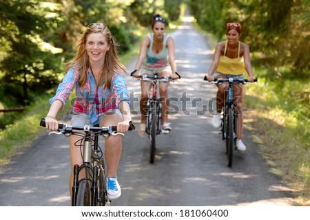 Three female friends riding bikes in park enjoy summer sport - stock photo