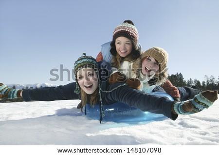 Three female friends sledding at winter time - stock photo