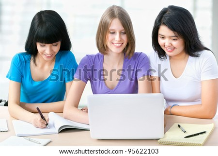 Three female friends studying together in a classroom - stock photo