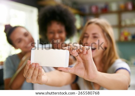 Three Female Friends Taking Selfie In Kitchen - stock photo