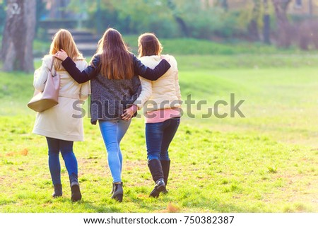 Three female friends walking in park
