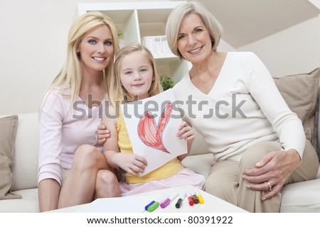 Three female generations of one family at home. Mother, grandmother and daughter who is holding a hand drawn picture of a red heart. Love or healthy living concept. - stock photo