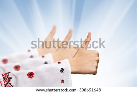 Three female hands in the Ukrainian national clothes shows symbol ok with thumbs up against Ukrainian flag background with sun light