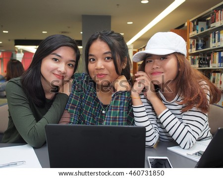 Three female students working on school assignment in the library