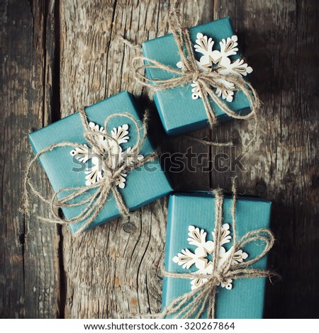 Three Festive Boxes in Blue Paper Decorated with Snowflakes and Linen Cord on Wooden Table. Top View - stock photo