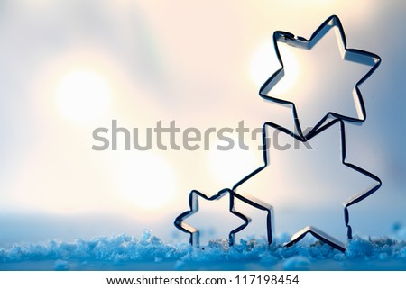 Three festive star cookie cutters balanced on blue wintery snow crystals outlined against soft muted lights with copyspace for your Christmas greeting - stock photo